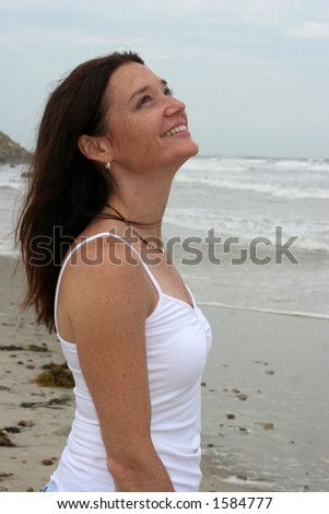 young woman on beach looking up - stock photo