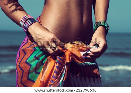 young woman on beach tiedown colorful sarong wearing beautiful braceletes - stock photo