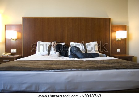 Young woman on bed in hotel room with nice interior design