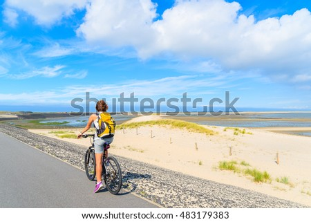 Young woman on bike during trip along coast of Sylt island near List village, Germany.