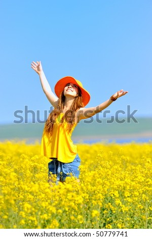 young woman on blooming rapeseed field - stock photo