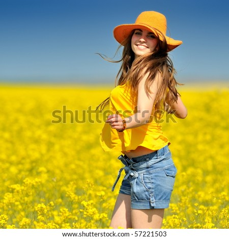 young woman on blooming rapeseed field in summer - stock photo