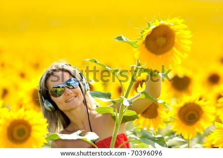 young woman on blooming sunflower field in summer - stock photo