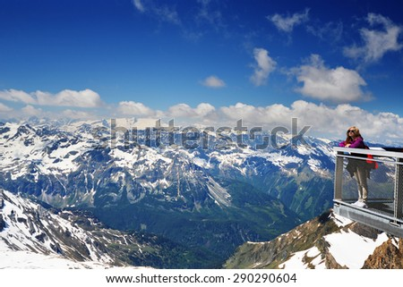 young woman on bridge,  background of snowy mountains - stock photo