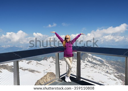 young woman on bridge,  background of snowy mountains