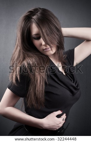 Young woman on dark wall background.