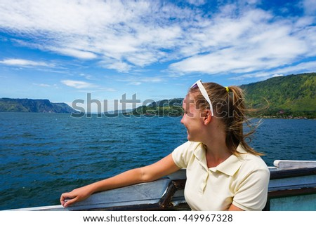 Young woman on ferry looking at Toba lake in North Sumatra, Indonesia. - stock photo