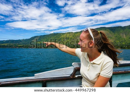 Young woman on ferry pointing at Toba lake in North Sumatra, Indonesia. - stock photo