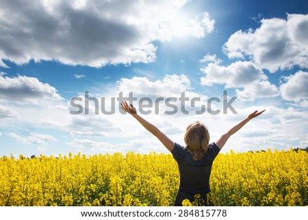 Young woman on field with yellow flowers