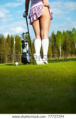 Young woman on golf course, back view - stock photo
