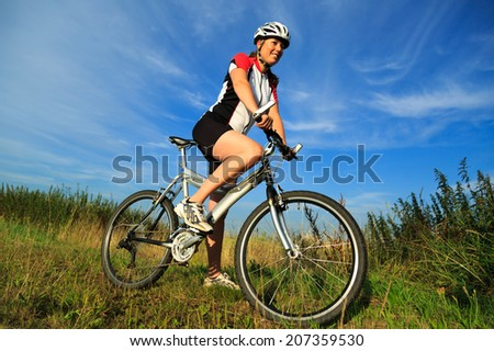 Young woman on her bicycle (MTB) in the countryside during a nice summer morning. - stock photo