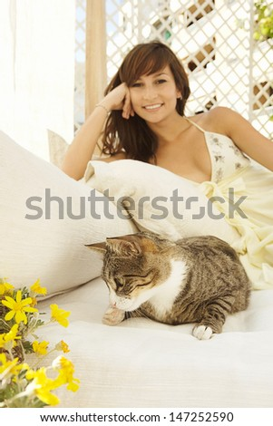 Little girl reading book to cat