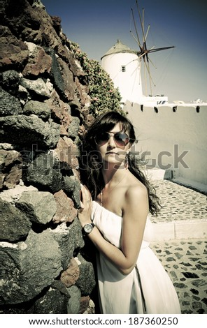 Young woman on holidays, Santorini Oia town. Photo in vintage style  - stock photo
