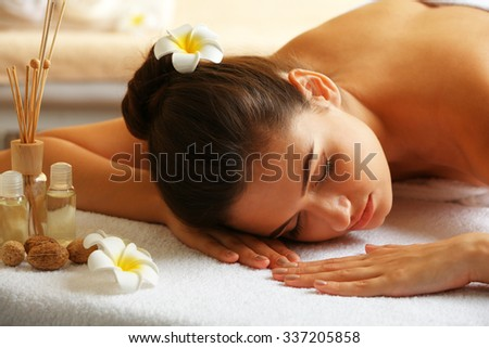 Young woman on massage table in beauty spa salon