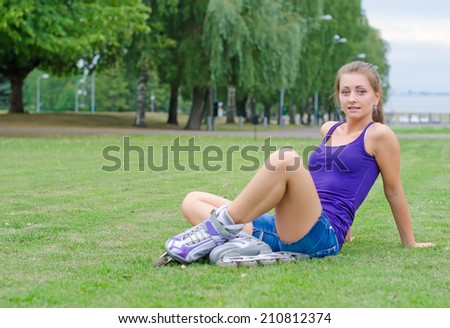 Young woman on roller skates in the park. - stock photo