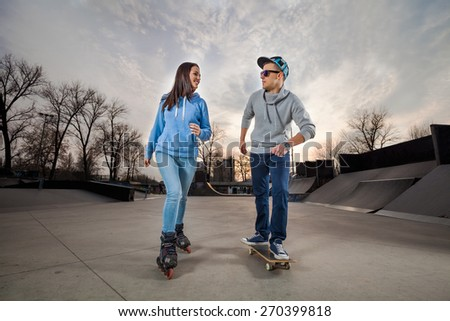 Young woman on rollerblades and young man on skateboard in a skate park - stock photo