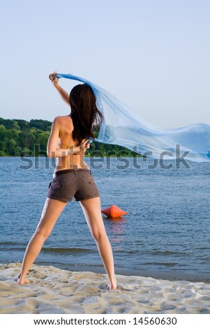 Young woman on sand beach near water with big cloth waving on wind - stock photo