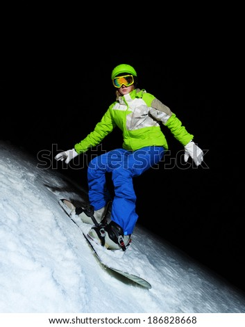 Young woman on snowboard at night - stock photo