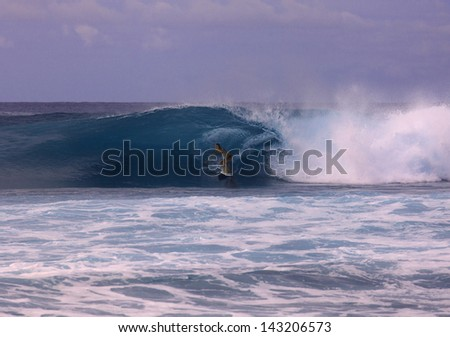 young woman on surfboard riding a big wave in hawaii