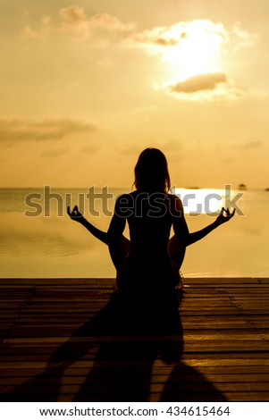 Young woman on the beach and enjoy the sunset - stock photo