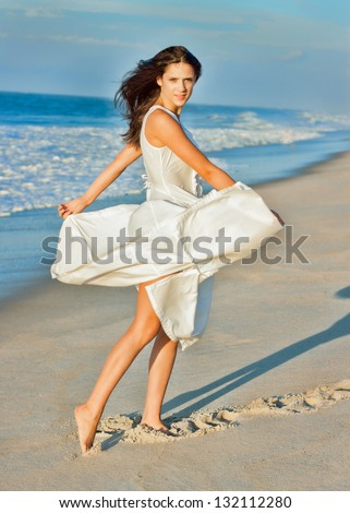 Young woman on the beach in a white dress