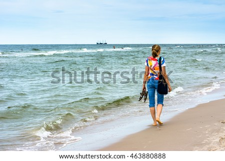 Young woman on the beach in summer, Baltic Sea in season, walking along sea shore