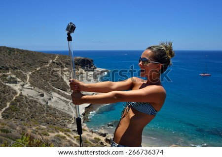 young woman on the beach in summer using camera - stock photo