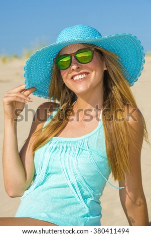 Young woman on the beach with pamela and blue shirt