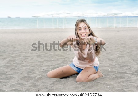 Young woman on the beach with sand slipping through her fingers - stock photo