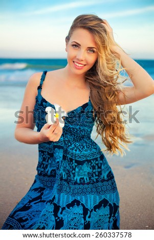 young woman on the beach with tropical flower Plumeria alba - stock photo