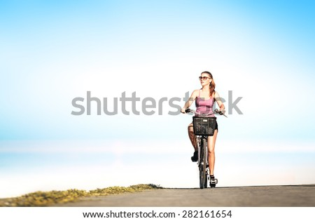 Young woman on the bicycle riding on road having fun and smiling - stock photo