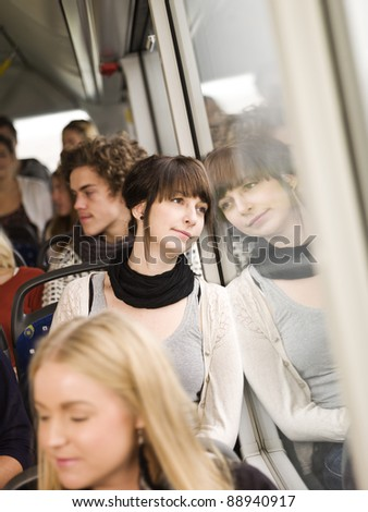 Young woman on the bus with large group of people - stock photo