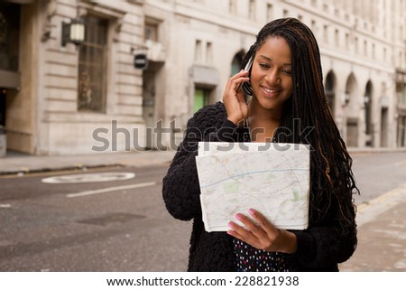young woman on the phone with a map. - stock photo