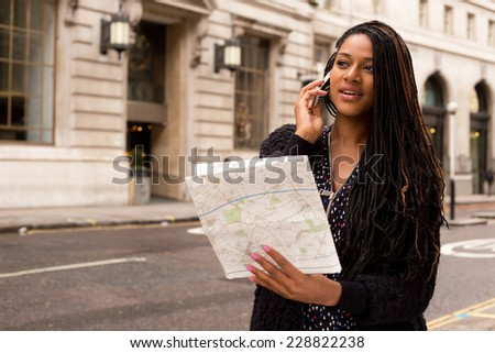 young woman on the phone with a map - stock photo