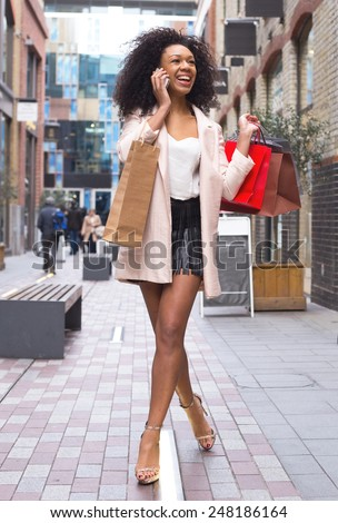 young woman on the phone with shopping bags - stock photo