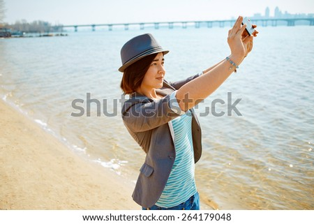 young woman on the sea beach at the morning. woman dressed in sneakers jeans jacket and hat. She is taking a selfie - stock photo