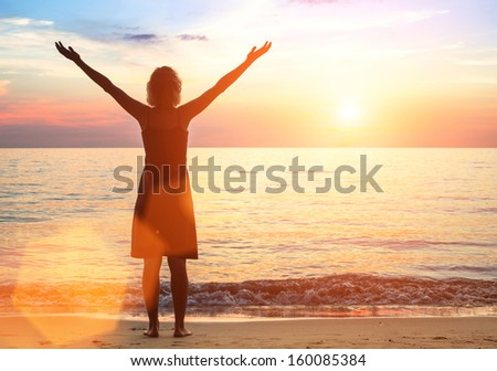 Young woman on the sea beach meets a beautiful sunset. - stock photo