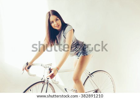 Young woman on white retro bicycle in studio. The sunlight from the window