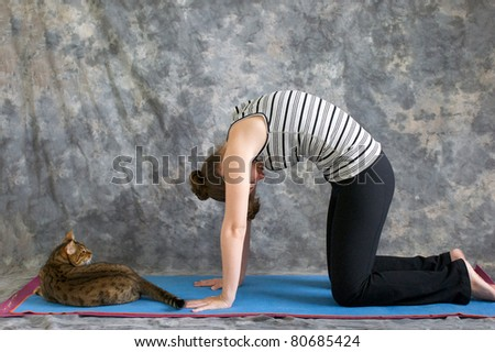 Young woman on yoga mat in  Yoga posture Marjaryasana or cat pose against a grey background in profile, facing left lit by diffused sunlight. A pet bengal cat is laying on the mat watching her.
