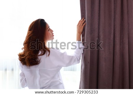 young woman open and holding the curtains to look out out side of new day