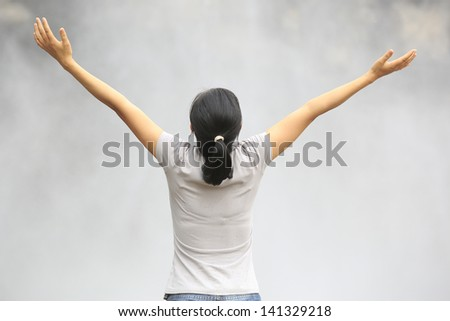 young woman open arms to waterfall - stock photo