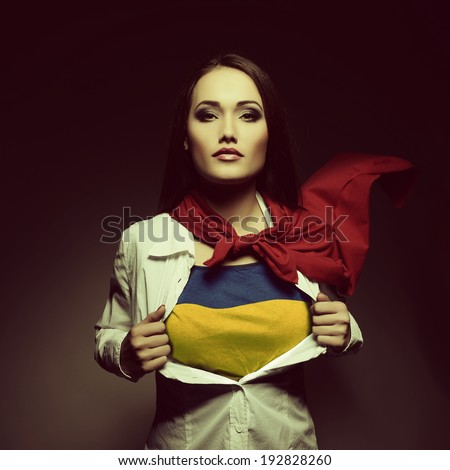 Young woman opening shirt painted in colors of ukrainian flag like superhero. Girl twenty-years-old like young Ukraine fights for independence, democracy and peaceful life. Ukrainian patriot concept. - stock photo