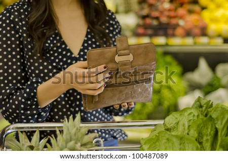 Young woman opening wallet at the supermarket