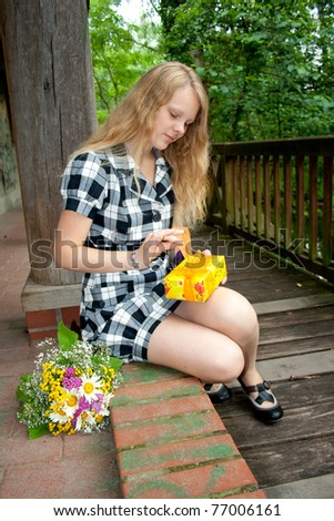 Young woman opens a gift - stock photo