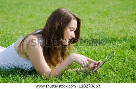 Young woman or student lying on her stomach in the green grass using a tablet notebook