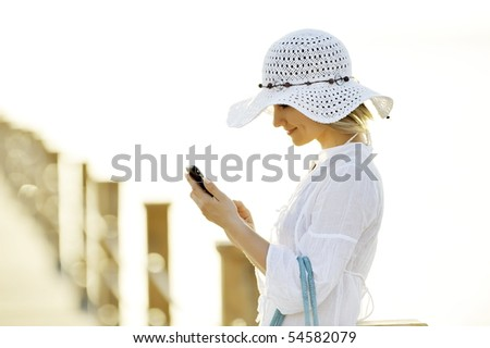 young woman outdoor in summer using cellphone - stock photo