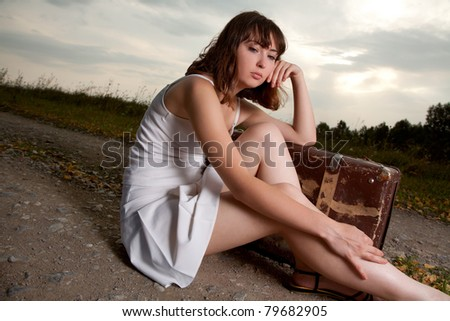 young woman outdoor sitting with her luggage