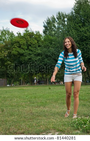 Young woman outdoor throwing a frisbee - stock photo