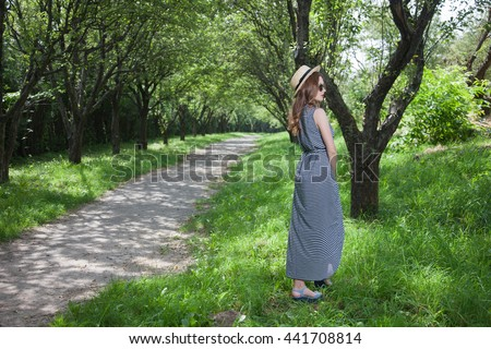 Young woman outdoors, apple orchard, avenue of trees