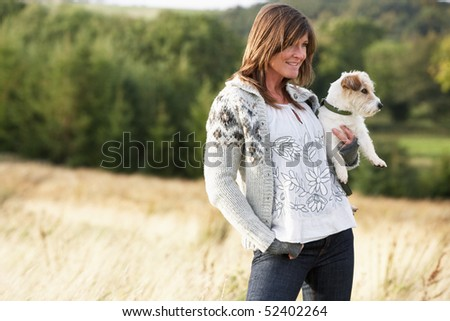 Young Woman Outdoors In Autumn Landscape Holding Dog